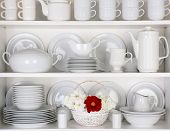 Closeup of white plates and dinnerware in a cupboard. A basket of white and red roses is centered on