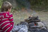 outdoor portrait of young child boy looking at fire