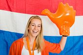 Portrait of happy young Dutch Sports fan wearing inflatable hand cheering, standing in front of the flag of the Netherlands