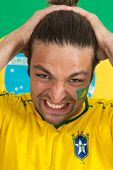 Despairing Brazilian sports fan, watching his national team fail in an important game