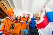 Excited young multiethnic soccer fans in Dutch national colors with tension and joy written on their faces, watching their national team perform well on television