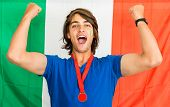 Italian sports fan, with a medal around his neck, cheering on Italy's national team, standing waist up in front of an italian flag