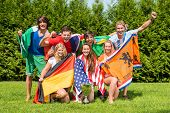 Portrait of cheerful young multiethnic athletes with various national flags celebrating in park