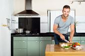 Portrait of handsome smiling man cutting vegetables at kitchen counter