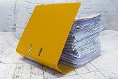 Heap Of Design And Project Drawings In Yellow Folder.