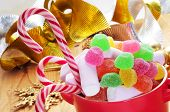 a bowl with different candies, such as candy canes, on a table with some christmas ornaments, such a