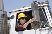 pic of logging truck  - Asian female industrial worker adjusting mirror while sitting in logging truck - JPG