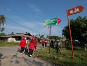 PADANG - AUGUST 25: Villagers return home after marketing in Padang, Sumatera, Indonesia on August 25, 2013. The signage shows a tsunami evacuation path which is a real and present danger here.