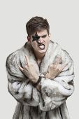 Portrait of frustrated young man in fur coat clenching teeth and making rebellious gesture against g