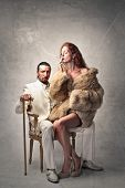 picture of gangster  - rich gangster in white dress sitting on an armchair and beautiful woman with fur smokes cigarette - JPG