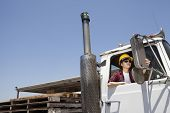 foto of logging truck  - Female industrial worker adjusting mirror while sitting in logging truck - JPG