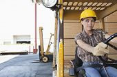 Female industrial worker driving forklift truck