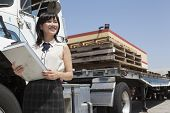 Young female holding clipboard while standing next to flatbed truck