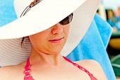 portrait of a girl in a white hat with a wide brim on the beach