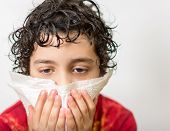 stock photo of blowing nose  - Hispanic child with curly hair suffering from the flu - JPG