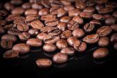 Fresh Roasted Coffee Beans On Black Shine Table. Closeup Photo