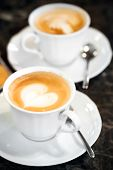 Two White Cups Of Cappuccino With Heart Shaped Milk Foam. Selective Focus