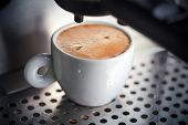 stock photo of mug shot  - White ceramic cup of fresh espresso with foam in the coffee machine - JPG