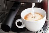 Coffee Maker Pouring Hot Milk Foam In Espresso Coffee To Prepare Cappuccino