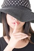 Close-up portrait of asian woman saying hush be quiet. Half covered face by black hat. Isolated on t