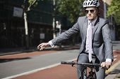 Young businessman showing hand sign while riding bicycle