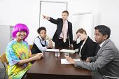 Angry multiethnic businesspeople with colleague in pink wig at meeting