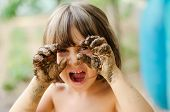 stock photo of mud  - Happy girl playing with mud with dirty hands - JPG