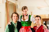 Young couple in traditional Bavarian Tracht in restaurant or pub, they might be the innkeepers with