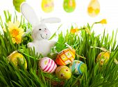 Colored easter eggs and rabbit on green grass