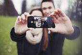 stock photo of love making  - Mixed race young boy and girl making a funny face while taking a self portrait with mobile phone - JPG