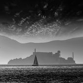 Alcatraz island penitentiary at sunset backlight sailboat in san Francisco California USA