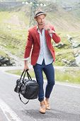 picture of a young fashion man walking on the middle of the road while holding a bag in his hand and