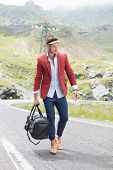 picture of a young fashion man walking on the middle of the road in the mountains while holding a ba