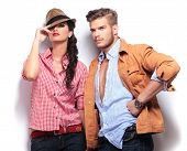 young casual fashion models posing in studio, woman looking at the camaera and man looking away to his side