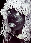 creative make up like Ethiopian mask, white pattern on black face close up