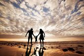 Happy family together hand in hand on the beach at sunset, summer time. Mother, father and a little