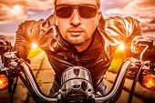 Biker man wearing a leather jacket and sunglasses sitting on his motorcycle looking at the sunset. Filter applied in post-production.