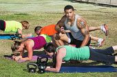 image of rep  - Instructor with tattoo helping bootcamp fitness students - JPG