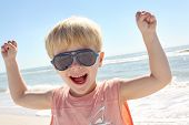 Young Child Flexing Muscles On Beach