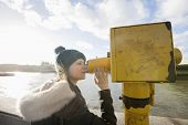 Side view of young woman in hooded sweatshirt looking through telescope by river Thames; London; UK