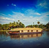 Vintage retro hipster style travel image of Kerala travel tourism background - houseboat on Kerala b
