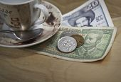 Cuban pesos and espresso coffee on wood table surface