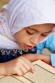 Little muslim girl reads holy Koran