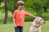 Happy young boy with pet dog standing at the park