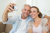 Happy couple taking a selfie together on the couch at home in the living room