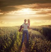 Man Carries Woman at Summer Field in Sunset