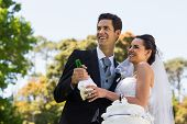 Happy young newlywed couple with champagne bottle at the park