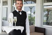 Handsome smiling waiter holding tray of champagne in the patio of restaurant