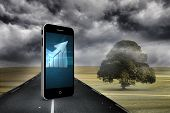 Arrow on smartphone screen against misty green landscape with street