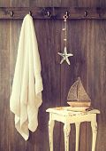 Bathroom with towel and toy boat on rustic table - vintage tone effect added